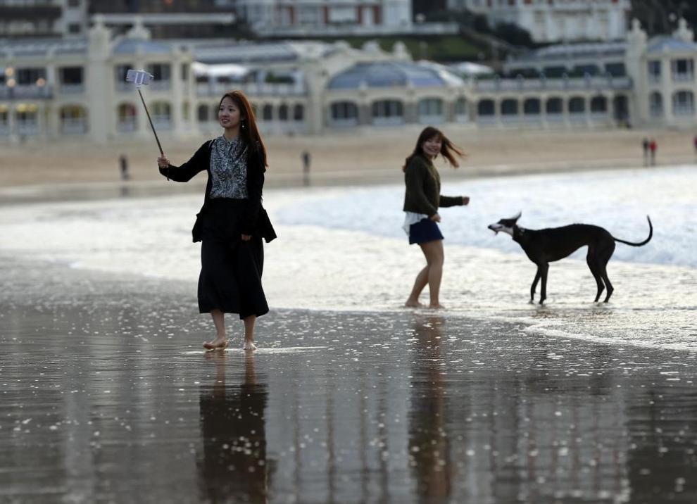 Una turista se fotografía en la playa de La Concha de San Sebastián.
