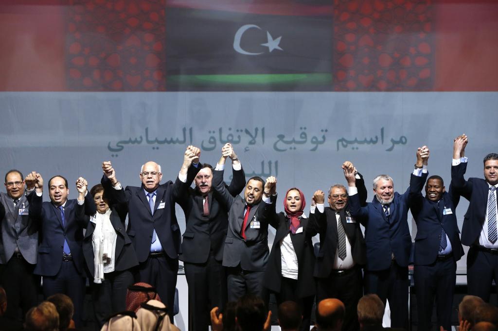 Los firmantes del pacto posan juntos y de la mano ante los medios de...