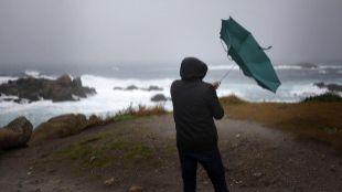 Un hombre ve como el viento le dobla el paraguas en A Coruña.