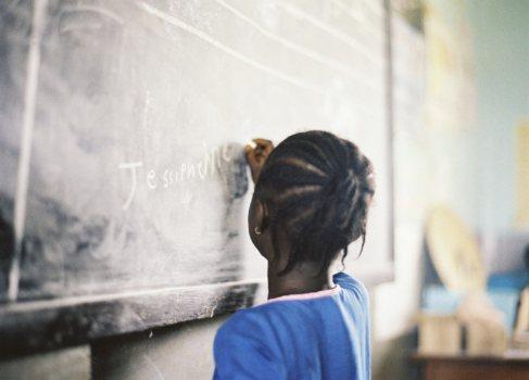 Una niña escribe su nombre en un programa de Plan Internacional sobre...