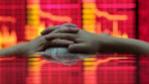 Un inversor contempla un panel bursátil en Shanghai