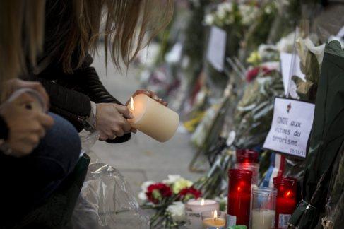 Una chica enciende una vela en la puerta de la embajada de Francia en...