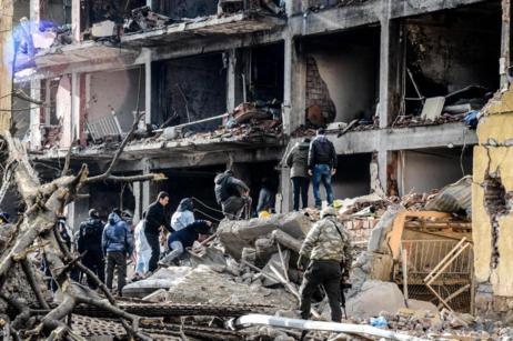 Varias personas frente al edificio calcinado tras la explosión en...