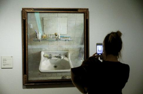 Una mujer fotografía ayer el cuadro de Antonio López 'Lavabo y...