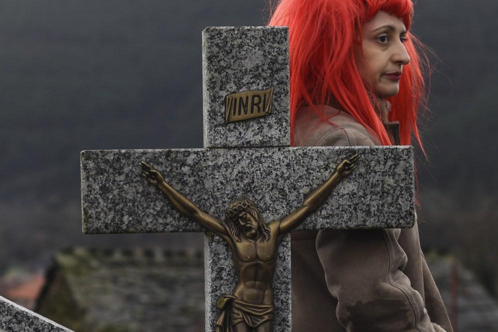 Una mujer con peluca pasa junto a una cruz en un cementerio durante el...