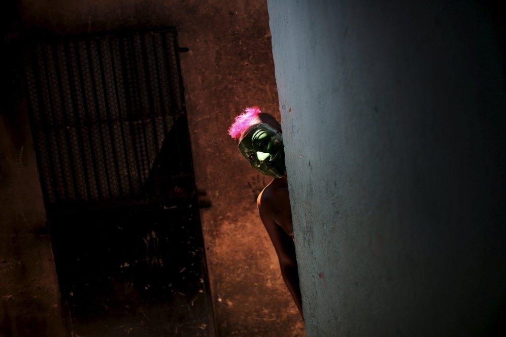 Un niño enmascarado se asoma por una esquina durante una de las...