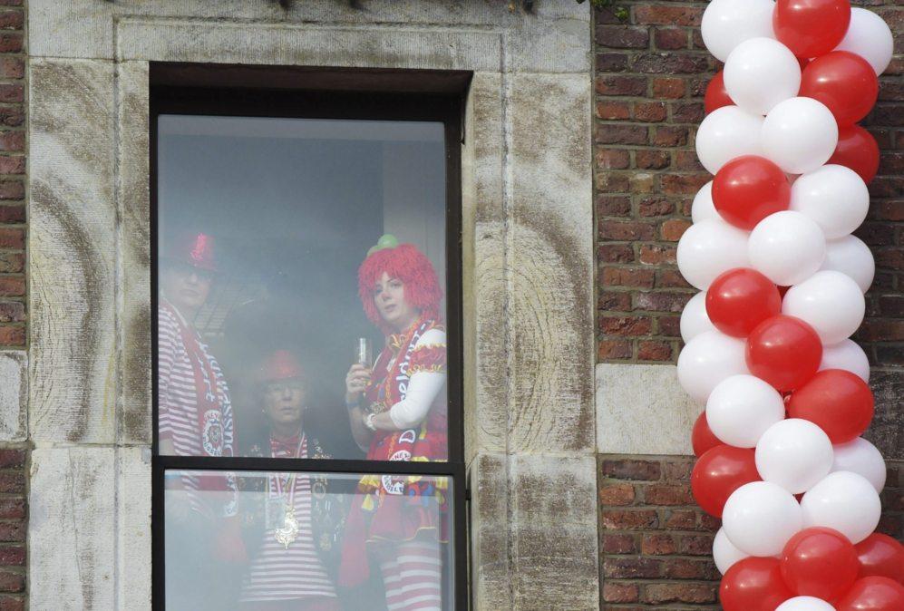Varias personas disfrazadas observan desde una ventana tras la...