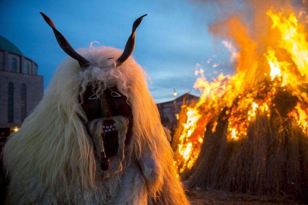 Un hombre viste un traje de piel de oveja delante de una hoguera en la...