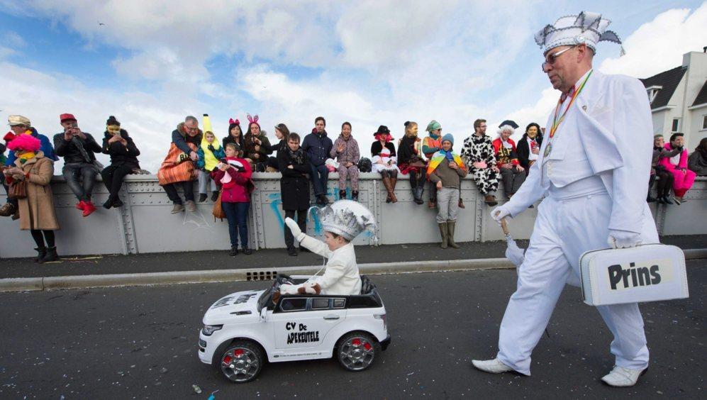 Un niño saluda a los espectadores mientras se pasea en un pequeño...