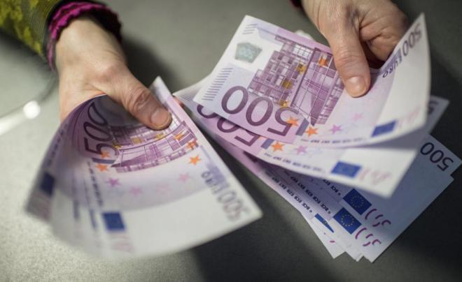 Un empleado de banca muestra billetes de 500 euros