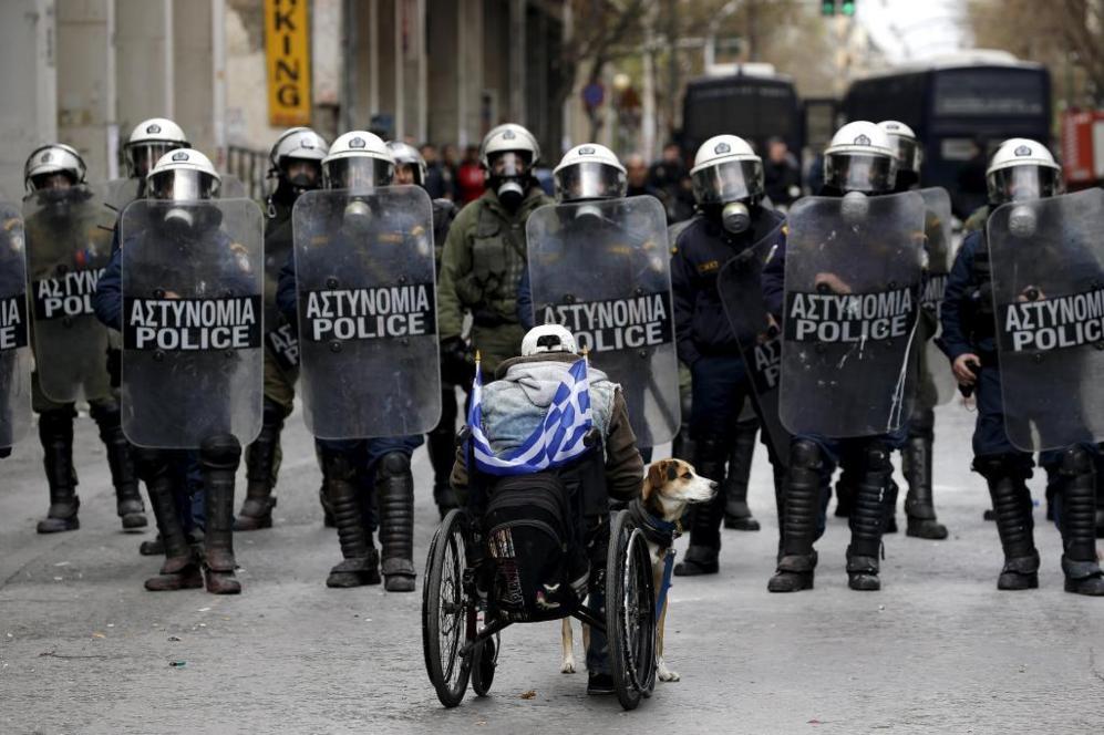 Un manifestante en silla de ruedas hoy en Atenas junto a su perro...