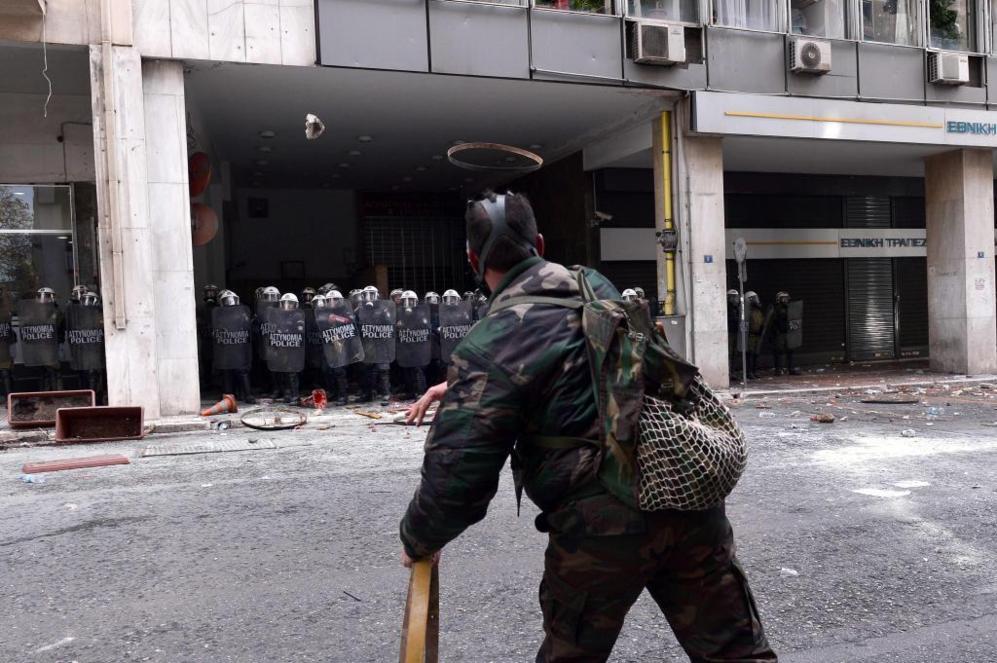 Uno de los manifestantes arrojando un objeto a la policía mientras...