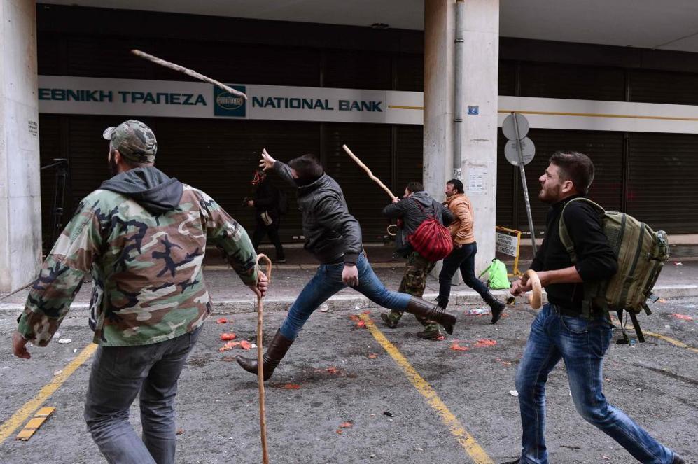 Varios manifestantes arrojando cayados y palos contra la policía en...