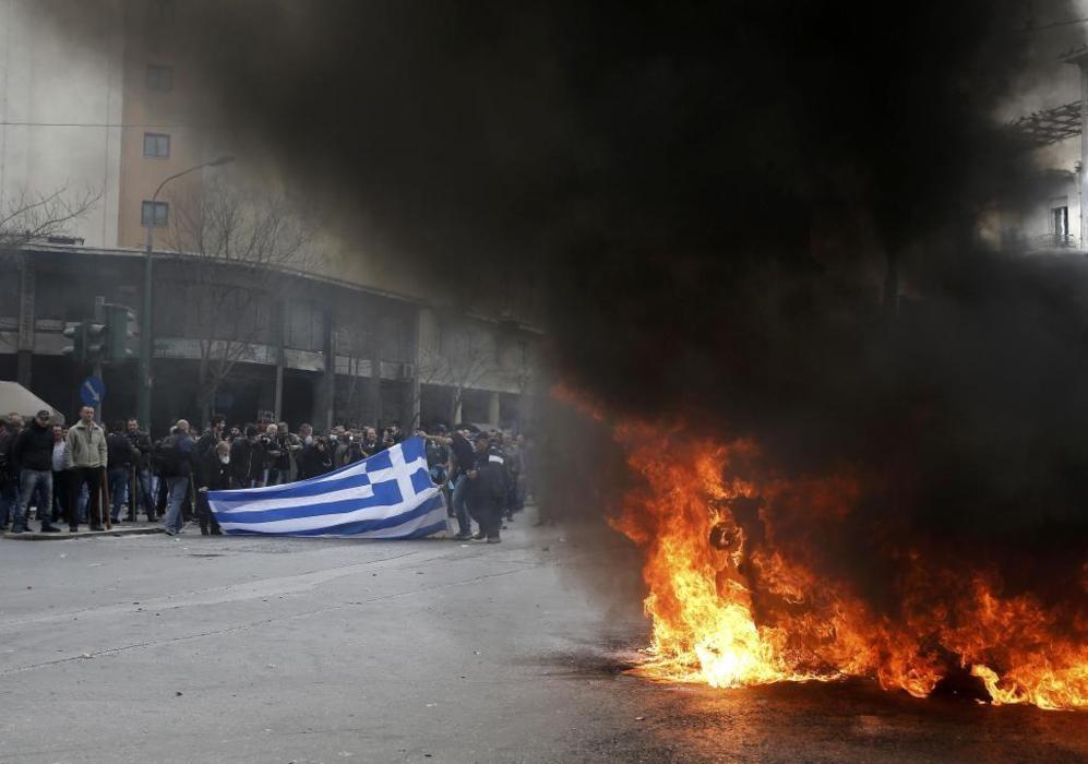 Un grupo de manifestantes sostienen una bandera de Grecia ante un...