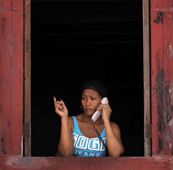 Una mujer habla por teléfono en la ventana de su casa en La Habana...