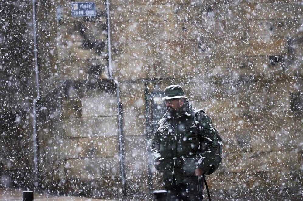 Una persona camina entre los copos de nieve en una calle de Reinosa...
