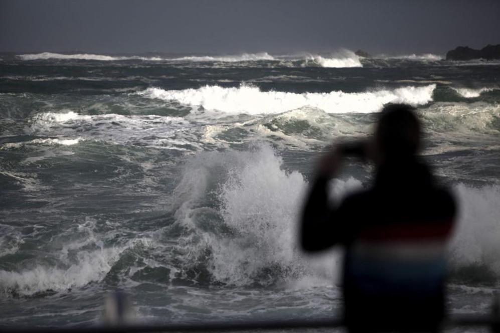 Un hombre hace fotos al fuerte oleaje registrado hoy en la costa de A...
