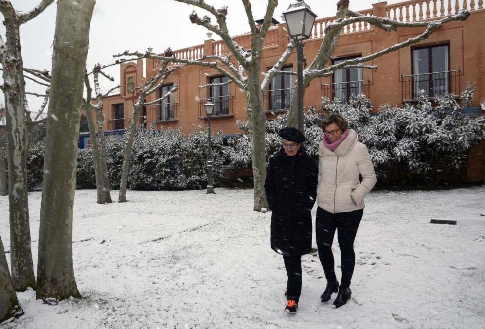 Dos mujeres pasean por la nieve en Torrecaballeros (Segovia).