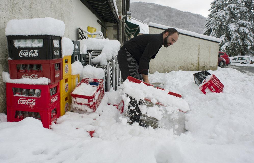 Un hombre retira la nieva acumulada a la entrada de un restaurante en...