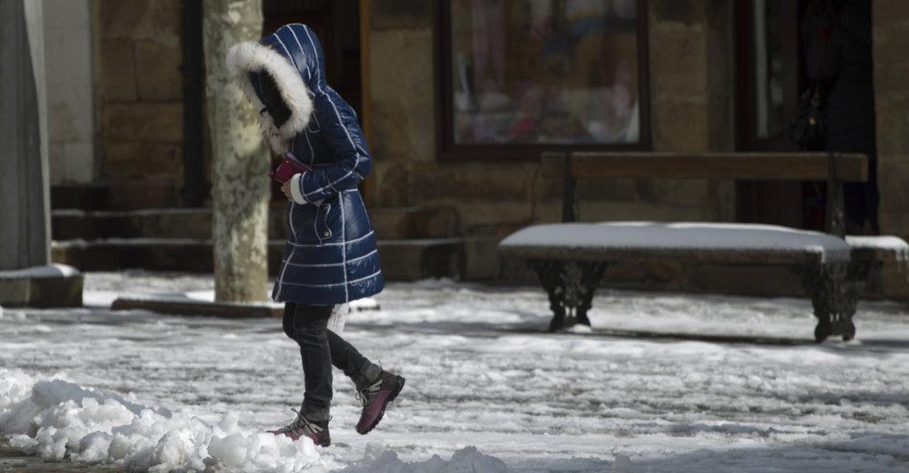 Una persona camina sobre la capa de nieve que ha cubierto las calles...