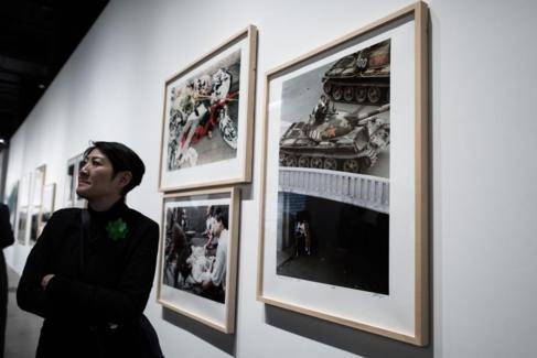 Una mujer observa las fotografías de Liu Heung Shing en la...