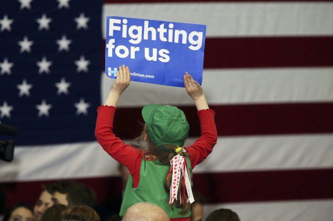 Una niña muestra un cartel de apoyo a la candidata demócrata,...