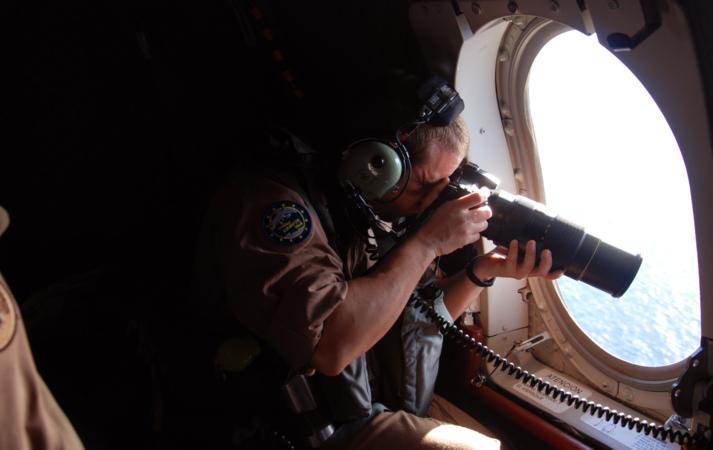 Un militar español toma fotografías desde el avión de vigilancia...