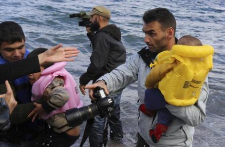 El fotógrafo Aris Messinis carga con un niño en la orilla de Lesbos.