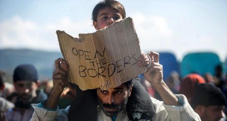 """Un hombre con su hijo, que lleva escrita la frase """"Abrid las..."""