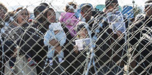 Un grupo de refugiados aguarda en la frontera entre Grecia y...