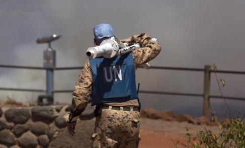 Un casco azul trasnporta equipación en la frontera entre Siria e...