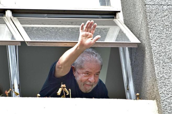 Luiz Inácio Lula da Silva saluda a sus seguidores desde una ventana...