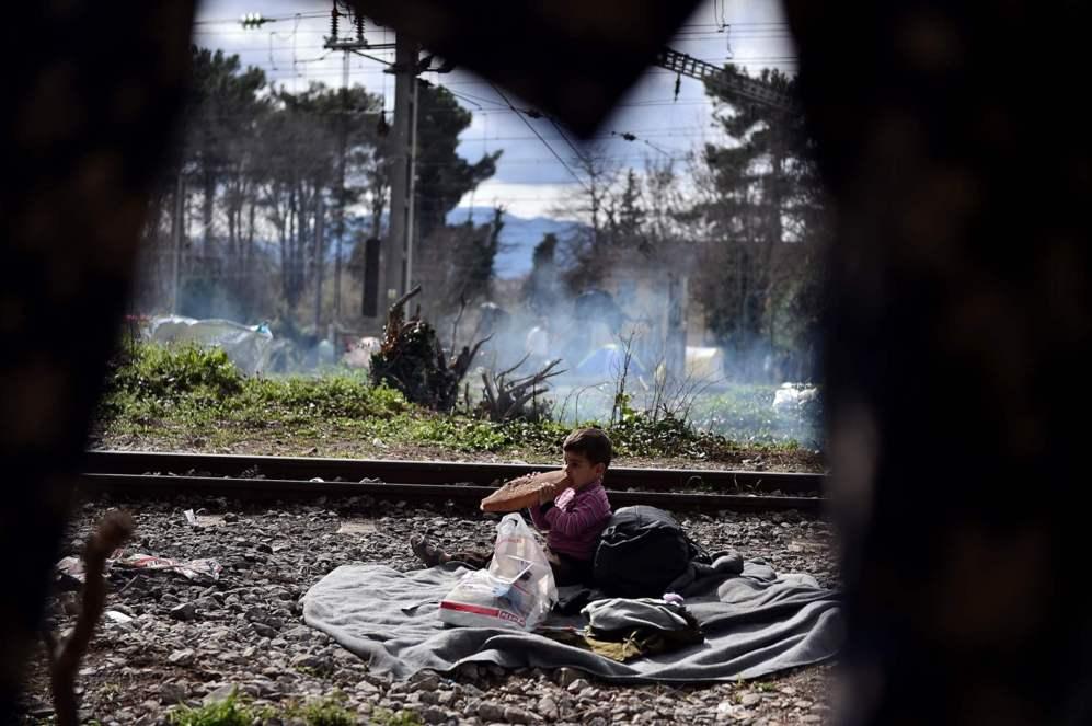 Un niño come pan entre unas vías de tren en Idomeni, en la frontera de Grecia con Macedonia.