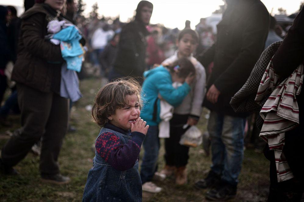 Una niña llora mientras sus padres esperan para recibir alimentos en un campo improvisado junto a la frontera de Grecia con Macedonia.