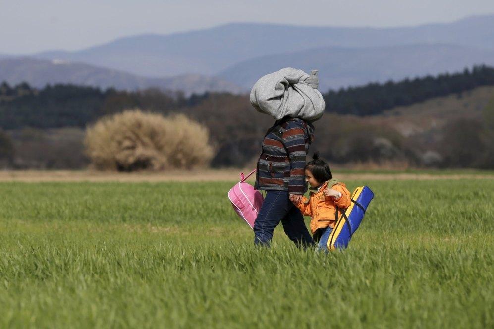 Una mujer camina con una niña por un campo junto a la localidad griega de Idomeni.