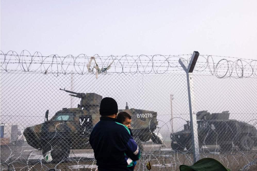 Un hombre sostiene un bebé mientras observa los vehículos militares junto a la valla que separa Grecia y Macedonia.