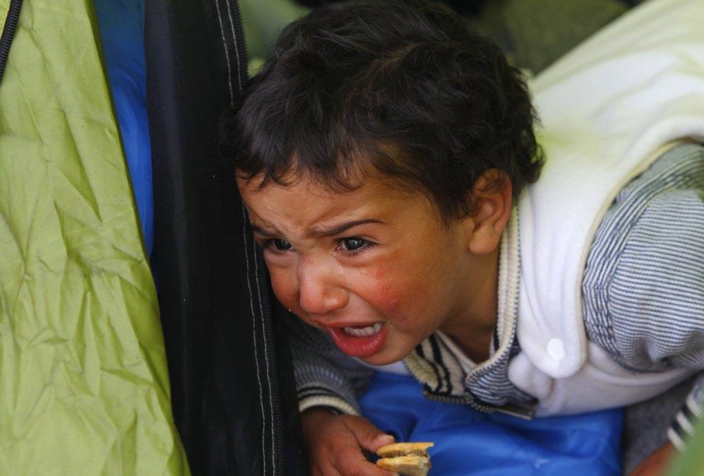 Un niño llora en el interior de una tienda en el campo improvisado en Idomeni junto a la frontera con Macedonia.