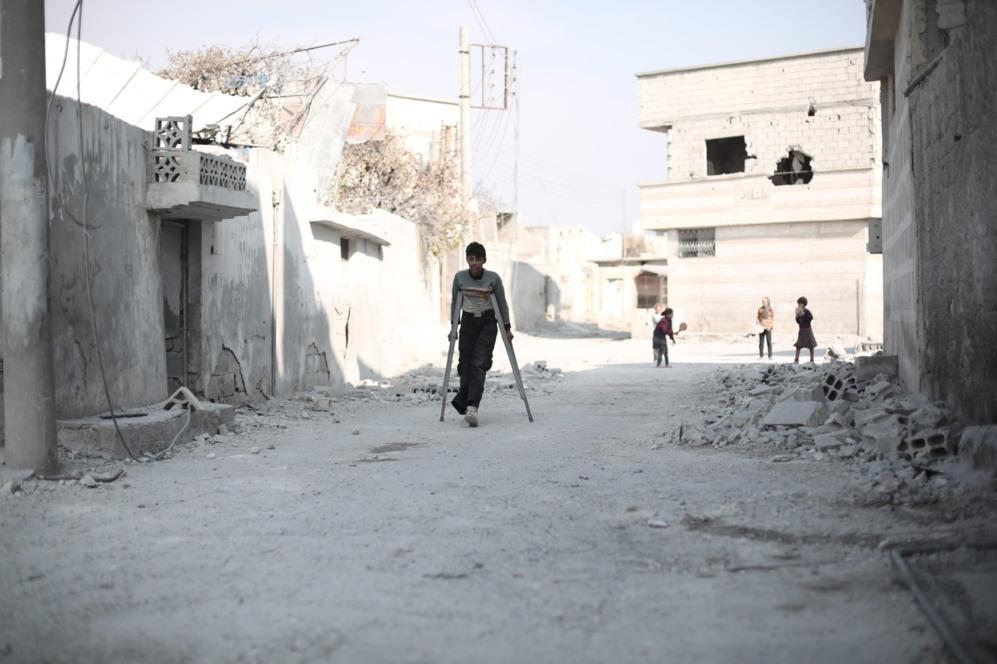 Un niño desplazado de un pueblo cercano camina por una de las calles...