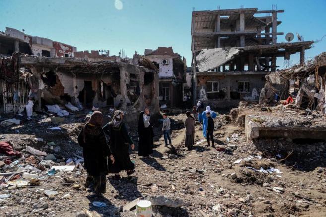Varias personas caminan entre las ruinas de Cizre, en Turquía.