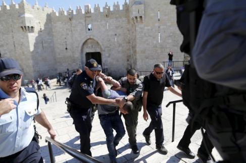Un palestino es detenido por policías israelíes cerca de la Puerta...