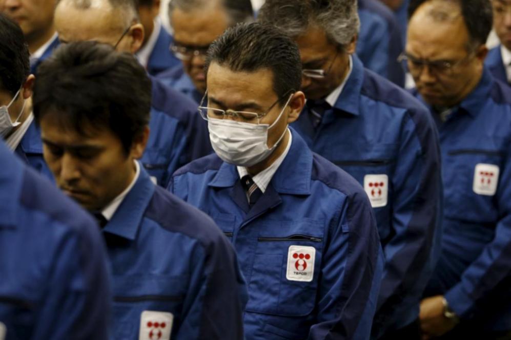 Trabajadores de Tepco guardan un minuto de silencio en Tokio.