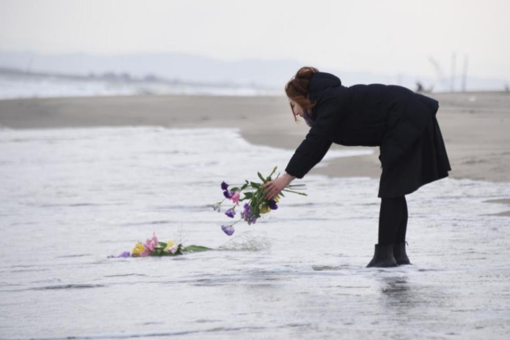 Una mujer lanza flores al mar en Sendai, al norte de Japón.