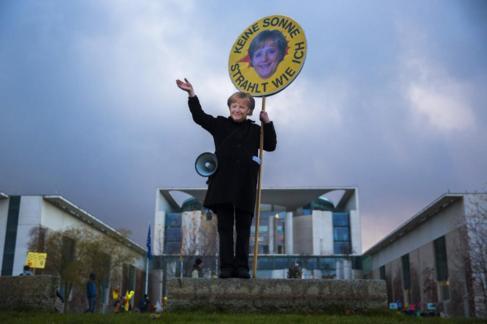 Un manifestante con una pancarta de  Merkel en una protesta...