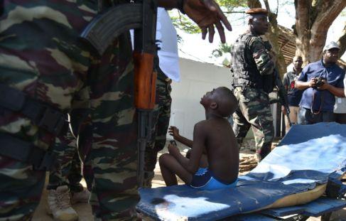 Un joven marfileño herido en los ataques rodeado de fuerzas de...