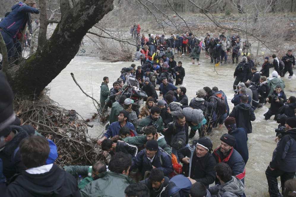Los inmigrantes cruzan en masa un río próximo a la frontera hacia...
