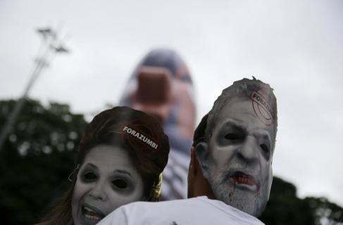Manifestantes con máscaras de Rousseff y Lula, el pasado domingo, en...