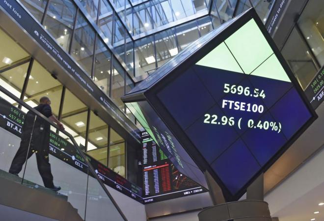 Un empleado de la Bolsa de Londres ante un panel con la cotización...