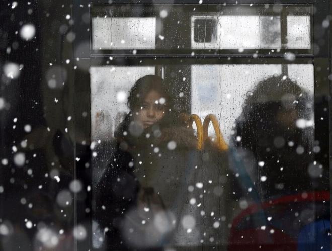 Una joven mira a través de la ventana de un autobús en Pamplona.