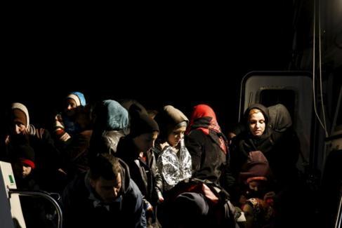Un grupo de refugiados sirios son atendidos a su llegada al puerto de...