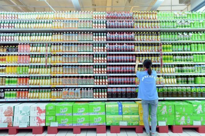 Empleada de un supermercado en China ordenando los productos.